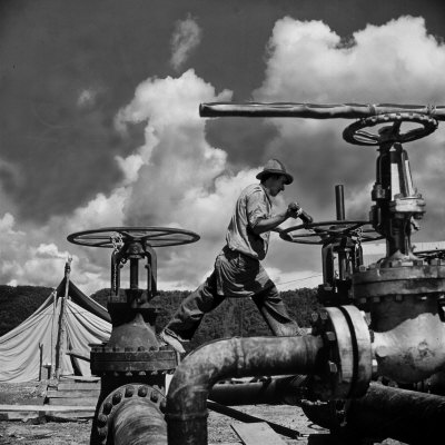 Worker Opening up a Pipeline to Let the Oil Flow Photographic Print by Thomas D. Mcavoy