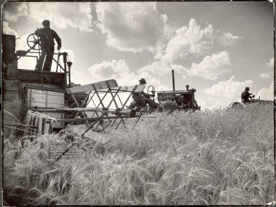 Kansas Farmer Driving Farmall Tractor as He Pulls a Manned Combine During Wheat Harvest Photographic Print by Margaret Bourke-White
