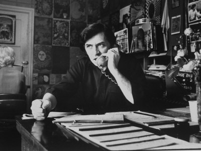 Bill Graham, Owner of Filmores East and West, Talking on Phone as He Works in His Office Photographic Print by John Olson