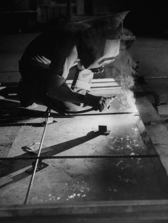 Man Welding Pieces of Metal Together Photographic Print by Allan Grant