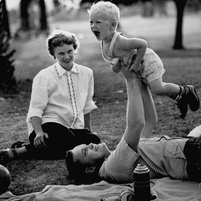 Father Playing with His Child During a Picnic Photographic Print by Allan Grant