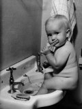 Adorable Baby Brushing Teeth While Sitting in Sink Lámina fotográfica