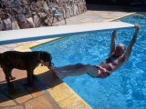 Sen. Barry Goldwater Hanging Underneath Diving Board in Swimming Pool as Dog Licks His Toes Premium Photographic Print by Bill Ray