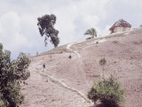 People Walking up a Path on a Hillside Towards a Hut in Rural Haiti Premium Photographic Print by Lynn Pelham