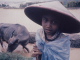 Indonesian Child Wearing a Hat Standing Near Rice Paddy with a Water Buffalo Premium Photographic Print by Co Rentmeester