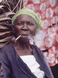 Old Haitian Woman Smoking a Pipe in Front of Her Hut Premium Photographic Print by Lynn Pelham