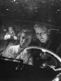 Young Couple Snuggling in Convertible as They Intently Watch Movie at Drive-in Movie Theater Photographic Print by J. R. Eyerman