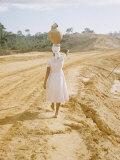 Brazilian Woman Walking Down a Sandy Road Carrying a Large Jar on Her Head Premium Photographic Print by Dmitri Kessel