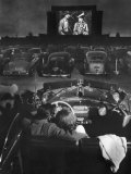 Young Couple Snuggling in Convertible as They Watch Large Screen Action at a Drive-In Movie Theater Photographic Print by J. R. Eyerman
