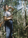 Young Hunter Blowing a Duck Decal Wistle while Holding His Rifle under His Arm Fotografisk tryk af Al Fenn