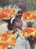 Two Haitian Boys Carrying Bouquets of Flowers Premium Photographic Print by Lynn Pelham