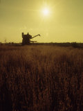 Combine Harvester in Field at Sunset Photographic Print by John Zimmerman