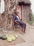 Old Haitian Woman in Front of Her Hut Premium Photographic Print by Lynn Pelham