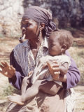Haitian Woman Smoking a Pipe while Holding a Baby Photographic Print by Lynn Pelham