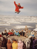 Native Alaskans Playing a Game of Nulukatuk, in Which Individals are Tossed into the Air Premium Photographic Print by Ralph Crane