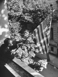 Man Hanging the American Flag Out of the Osteopath's Office Window During WWII Photographic Print by George Strock
