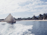 Haitian Beach Scene with a Fishing Boat Coming on Shore Premium Photographic Print by Lynn Pelham