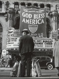 Man with Shopping Bags in Front of Million Dollar Theatre Emblazoned with God Bless America Banner Premium Photographic Print by Bob Landry