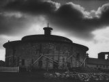 Round Stone Shaker Barn Dramatically Highlighted with Darkening Clouds Premium Photographic Print by John Loengard