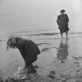Girl Playing in the Sand while an Older Woman Gets Her Feet Wet in the Ocean at Blackpool Beach Photographic Print by Ian Smith