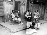 African American Women Sitting on the Porch of their Ramshackle House Watching their Children Play Photographic Print by Alfred Eisenstaedt