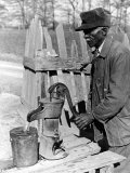 Old African American Sharecropper Dave Alexander Using Water Pump to Draw Water Premium Photographic Print by Alfred Eisenstaedt