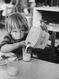 Child Pouring a Glass of Milk at Day Care Premium Photographic Print by Leonard Mccombe