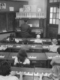 Elementary School Music Teacher Playing F-Major Chord on Piano, Keys Light up on Plastic Keyboard Premium fotoprint van Yale Joel