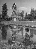 Boy Fishing in a River Reflecting a Dutch Windmill Premium Photographic Print by Bob Landry