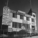 View of a Souvenir Store that Specializes in the Dionne Quintuplets Merchandise Photographic Print by Hansel Mieth