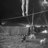 Two Small Children Watching Circus Performer Practicing on Tightrope, Her Legs Only Visible Photographic Print by Nina Leen