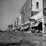 Mud and Wreckage are Piled in Front of Stores Along Desolate Main Street on North Topeka Photographic Print by Francis Miller
