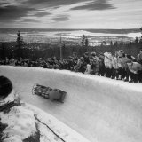 Bobsled Racing by on a Big Vendleboe Curve During the Winter Olympics Premium Photographic Print by Nat Farbman