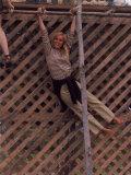 Barefoot Girl Swinging on Structure Containing Baby Chicks in Coop, Woodstock Music and Art Fair Premium-Fotodruck von John Dominis