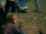 Jackie Barg Sitting on the Ground and Blowing Bubbles, During the Woodstock Music and Art Fair Premium Photographic Print by John Dominis