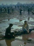 Chuck Morgan Sitting in the Mud and Water with a Friend, During Woodstock Music and Art Fair Premium Photographic Print by John Dominis