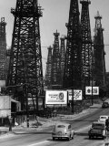 Car Traffic on Highway Next to Advertising Billboards and Oil Well Towers, Signal Hill Oil Field Photographic Print by Andreas Feininger