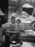 Father Sitting on Couch with Pigtailled Daughter Reading to Her the Sunday Comic Pages Premium Photographic Print by Nina Leen