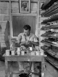 Shoemaker Sitting in His Shop Working on a Pair of Old Work Shoes Premium Photographic Print by John Phillips