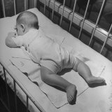 Baby Sleeping on its Stomach in Nursery at St. Vincent's Hospital Lámina fotográfica por Nina Leen