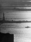 Moonlight on the Waters Surrounding Statue of Liberty as a Tug Boat Steams Past in New York Harbor Reproduction photographique sur papier de qualité par Andreas Feininger