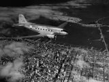 Plane Flying over a City from a Story Concerning United Airlines Premium Photographic Print by Carl Mydans