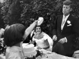 Flower Girl Janet Auchincloss Holding Up a Wedge of Wedding Cake for Bridegroom Sen. John Kennedy Photographic Print by Lisa Larsen