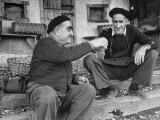 Two Older Basque Men Sitting on a Porch Toasting, as They Prepare to Drink Together Reproduction photographique sur papier de qualité par Dmitri Kessel