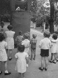 Kids Watching Outdoor Puppet Show Impressão fotográfica premium por Dmitri Kessel