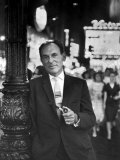 Playwright Moss Hart Holding Pipe While Leaning on Lamppost in the Middle of Times Square Premium Photographic Print by Alfred Eisenstaedt
