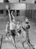 Five Young Boys Wearing Gym Clothes and Playing a Game of Basketball in the School Gym Photographic Print