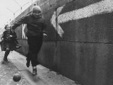 Young Boy and Girl Playing Soccer Next to the Berlin Wall Premium Photographic Print by Paul Schutzer