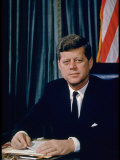 Pres. John F. Kennedy Sitting at His Desk, with Flag in Bkgrd Fotoprint van Alfred Eisenstaedt