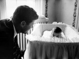 Sen. John F. Kennedy Playing Peek-A-Boo with His Daughter Caroline in Her Crib Photographic Print by Ed Clark